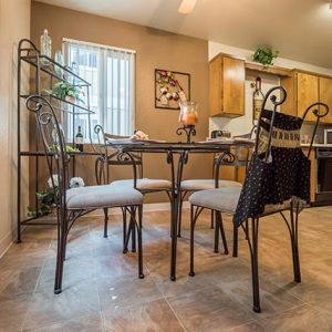 Model unit dining room and kitchen featuring custom cabinets, and appliances